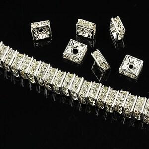 Distantiere argintii cu rhinestones albe 6mm (patrate 2,5x6mm)