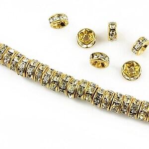Distantiere aurii cu rhinestones albe 6mm (rondele 2,5x6mm)
